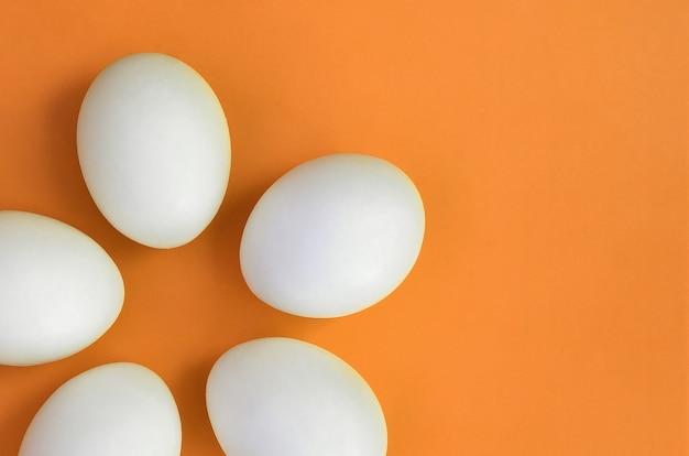Unos huevos de pascua blancos en naranja brillante