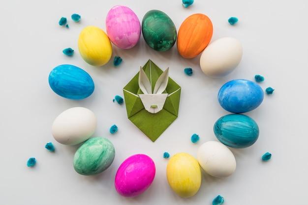 Huevos de pascua brillantes colocados alrededor de amentos de conejo y sauce de papel.