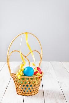Huevos de pascua brillantes pintados en una cesta de mimbre sobre una mesa de madera clara. espacio de copia