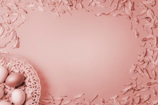 Huevos de pascua en una canasta y coloridos pétalos de flores de primavera de manzanilla y crisantemo sobre un fondo mate rojo rosa pálido.