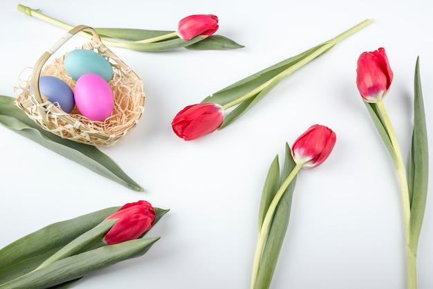 Huevos de pascua en canasta con tulipanes en mesa