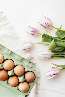 Huevos de pascua en cartón verde y tulipanes flatlay