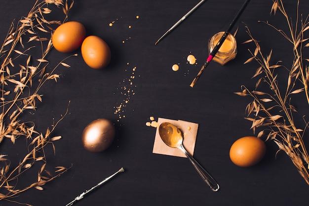 Huevos de pascua cerca de la cuchara en el papel y pincel en la lata de tinte entre la hierba seca y las manchas