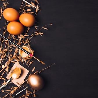 Huevos de pascua cerca de una cuchara sobre papel y pincel sobre una lata de tinte entre plantas secas