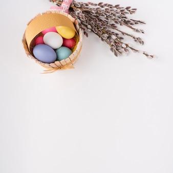 Huevos de pascua en cesta de madera con ramas de sauce.