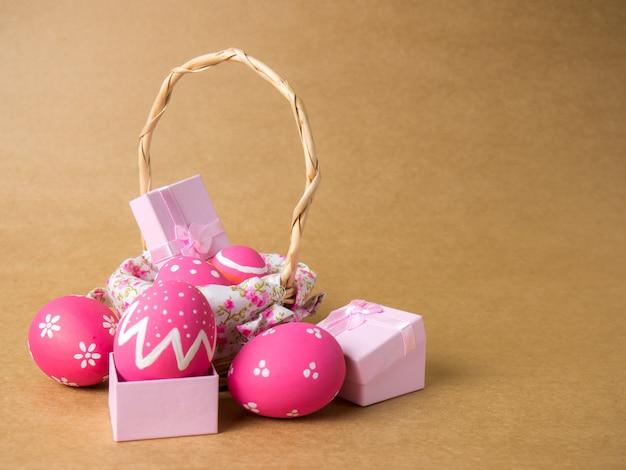 Los huevos de pascua en una cesta tejen madera en la esquina izquierda sobre un fondo marrón.