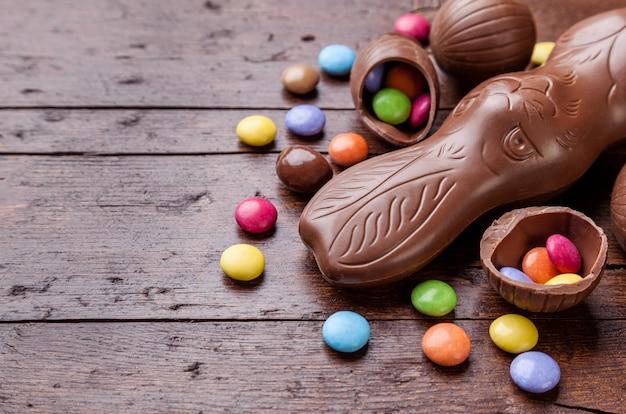 Huevos de pascua de chocolate y dulces en la mesa de madera