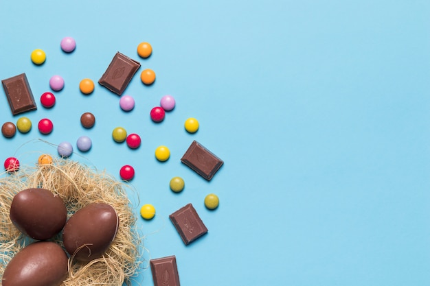Huevos de pascua de chocolate en un nido decorado con caramelos de gemas y trozos de chocolate sobre fondo azul