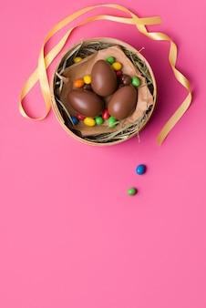 Huevos de pascua de chocolate sobre un fondo rosa.