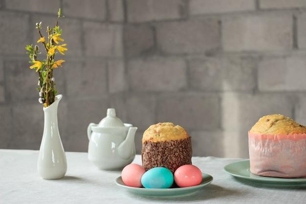 Huevos de pascua de color rosa pastel y azul, pan de pascua ruso y ortodoxo kulich o paska, jarrón con flores de forsitia de primavera y amentos de sauce en la mesa