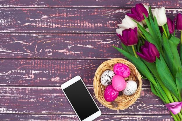 Huevos de pascua de colores, flores de tulipán y teléfono inteligente