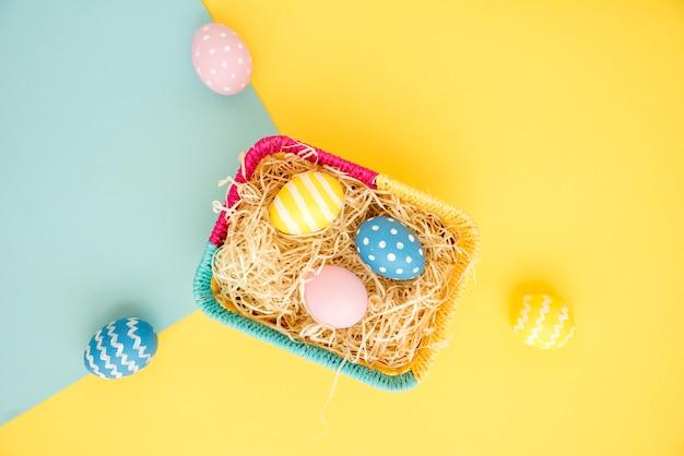Huevos de pascua coloridos en canasta pequeña