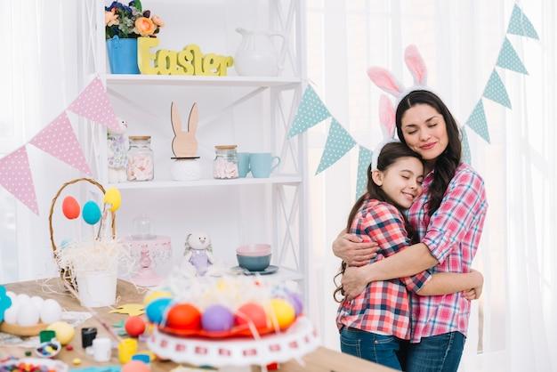 Huevos de pascua coloridos delante de la madre y la hija que se abrazan