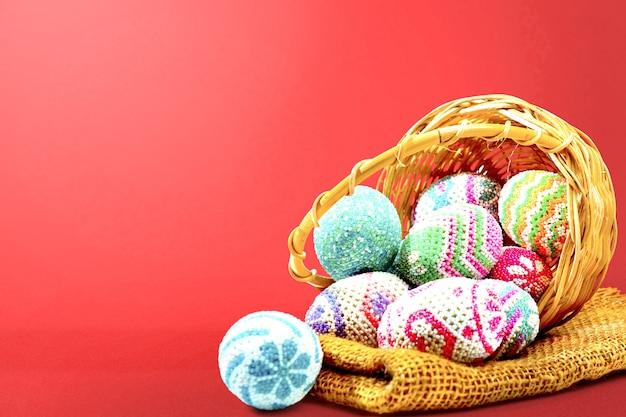 Huevos de pascua coloridos derramados de la canasta de madera con tela