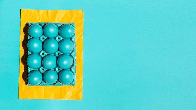 Huevos de pascua coloridos en estante en el papel amarillo en la tabla
