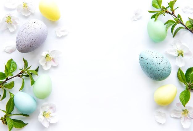 Huevos de pascua coloridos con flores de primavera en flor aisladas sobre fondo blanco.