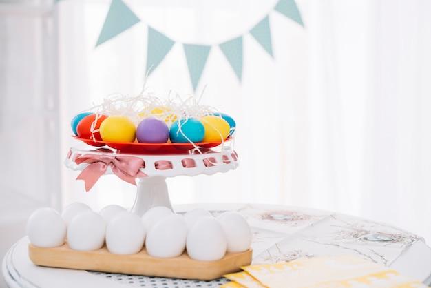 Huevos de pascua coloridos con los huevos blancos en la tabla en casa