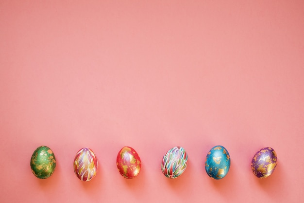 Huevos de pascua coloridos con lámina dorada sobre el fondo rosa brillante. copie el espacio. vacaciones de primavera.