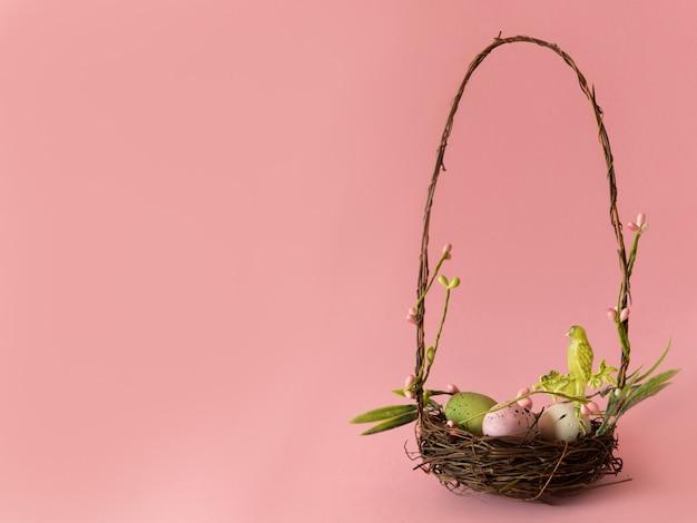 Huevos de pascua coloridos en poca cesta aislada en fondo rosado.