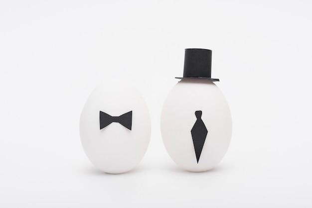 Huevos de pascua con corbata y sombrero en mesa