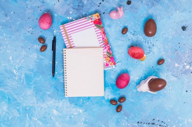 Huevos de pascua con cuaderno en blanco en la mesa