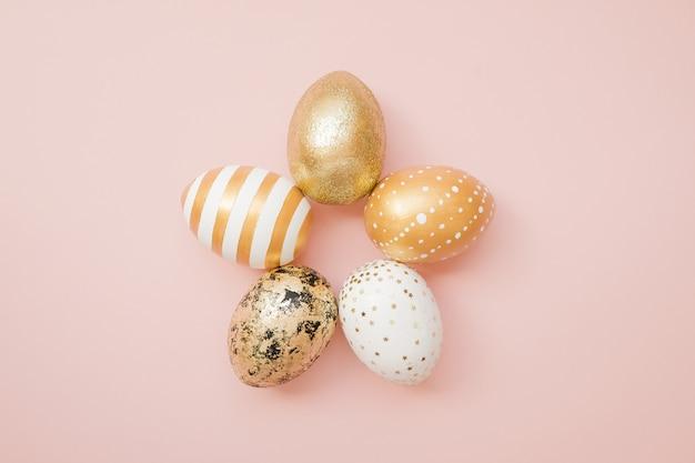Huevos de pascua decorados de oro sobre fondo rosa pastel