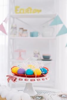Huevos de pascua decorativos frente a estante decorativo borroso