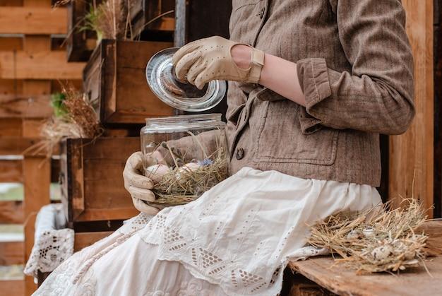 Huevos de pascua decorativos en un primer de cristal del tarro en sus rodillas y en las manos de una muchacha en ropa del vintage.