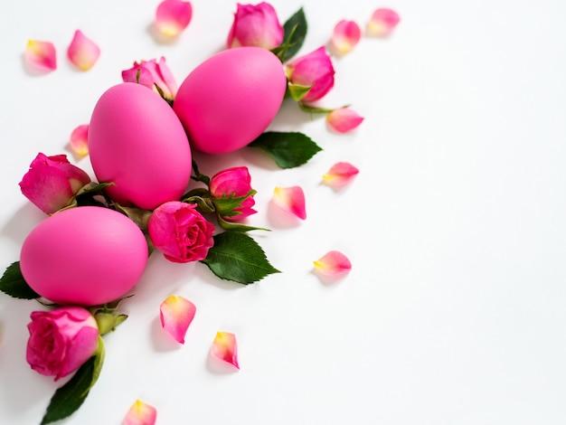 Huevos de pascua decorativos y rosas rosadas huevos de pascua rosados en fondo ligero. tarjeta de vacaciones