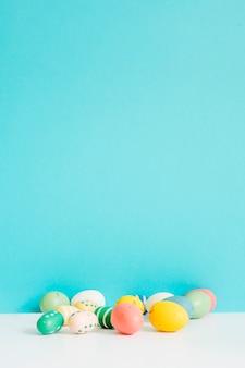 Huevos de pascua de diferentes colores en la mesa