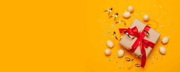 Huevos de pascua dorados decorados con regalos o cajas con arcos rojos y confeti.