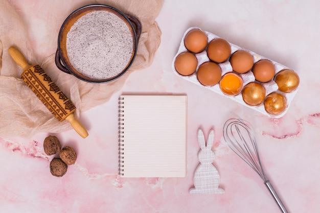Huevos de pascua dorados en estante con libreta, utensilios de cocina y conejo.