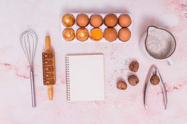 Huevos de pascua dorados en estante con notebook y utensilios de cocina.