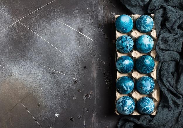 Huevos de pascua en envases de cartón pintados a mano en color azul.
