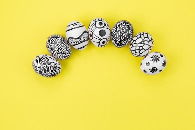 Los huevos de pascua están pintados en blanco y negro, abstracción, dispuestos en semicírculo. huevos de pascua pintados sobre un fondo amarillo. endecha plana. copia espacio