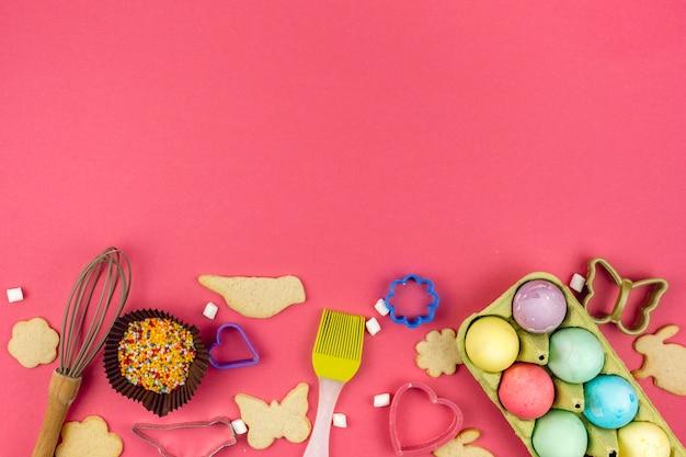 Huevos de pascua en estante con galletas y utensilios de cocina.