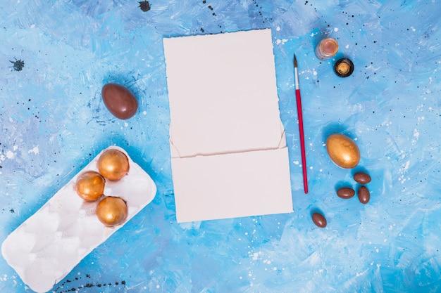 Huevos de pascua en estante con pincel y papel