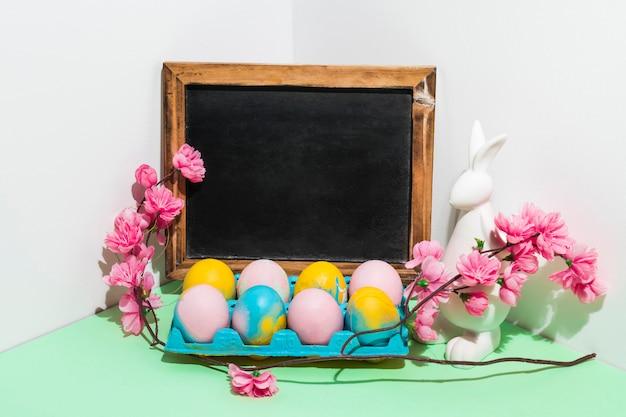 Huevos de pascua en estante con pizarra en blanco y flores en la mesa