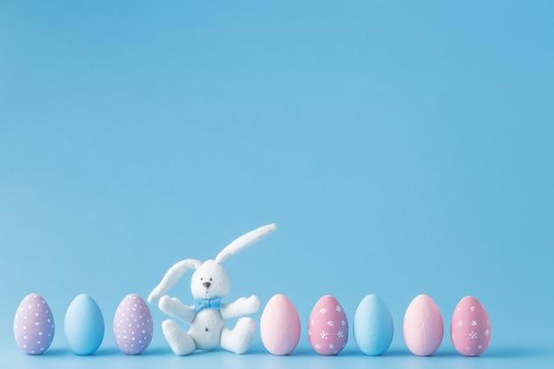 Huevos de pascua en una fila, sobre fondo azul.