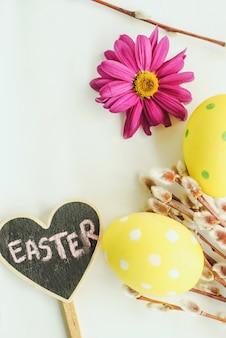 Huevos de pascua, flores de primavera y sauce sobre fondo blanco