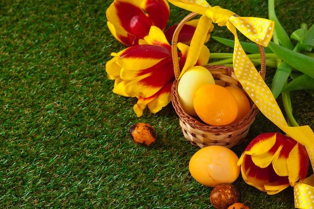 Huevos de pascua con flores sobre hierba verde