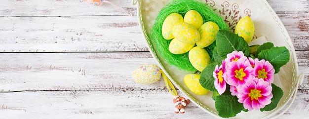 Huevos de pascua y flores sobre una mesa de madera clara. vista superior