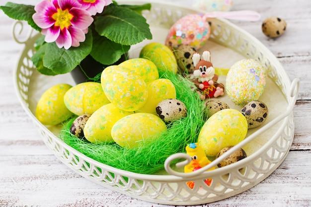 Huevos de pascua y flores sobre una mesa de madera clara