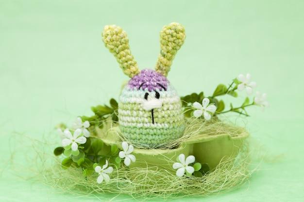 Huevos de pascua hechos a mano, flores, conejito sobre un fondo verde, amigurumi