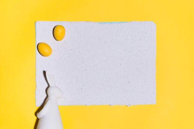 Huevos de pascua en hoja de papel con conejo en mesa amarilla