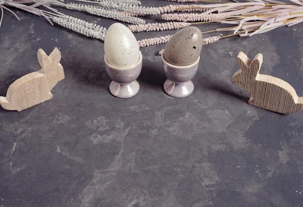 Huevos de pascua en huevera y decoración de conejito de madera.