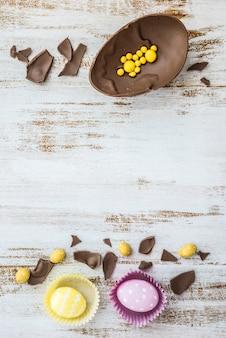 Huevos de pascua con huevo de chocolate en mesa
