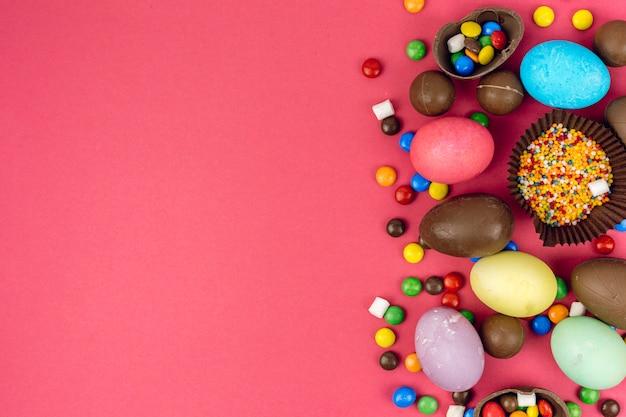 Huevos de pascua con huevos de chocolate y dulces en mesa