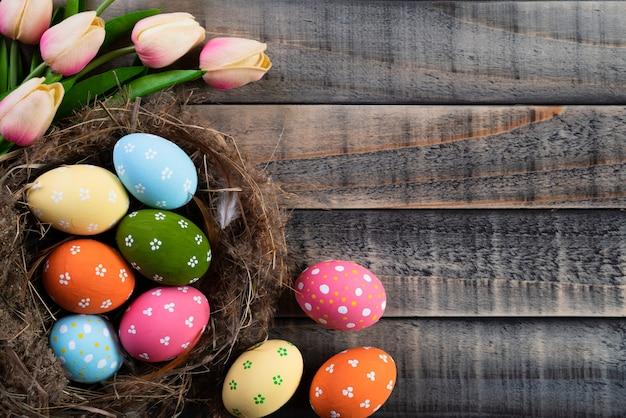 Huevos de pascua en jerarquía con los tulipanes y la pluma rosados en fondo de madera.