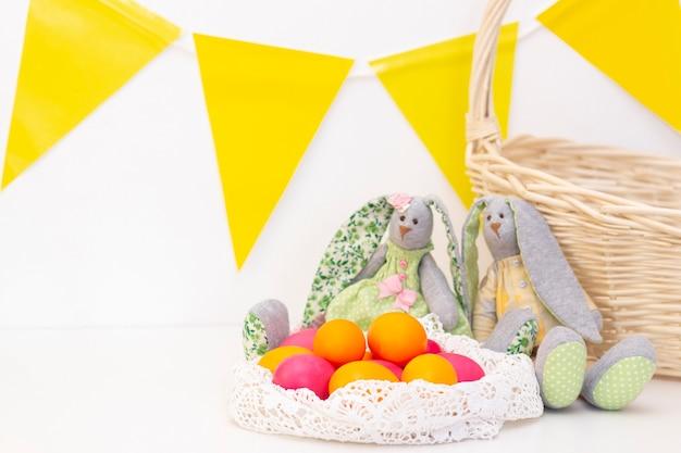 Los huevos de pascua lindos conejitos están en la canasta. felices pascuas. huevos pintados sobre un fondo claro.